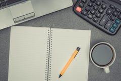 Ordinateur portable ou carnet, calculatrice et tasse de café sur le wor Images libres de droits