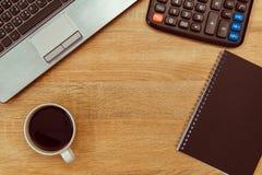 Ordinateur portable ou carnet, calculatrice et tasse de café sur le wor Photos stock