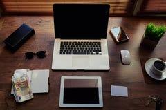 ordinateur portable portatif, comprimé numérique avec l'écran vide de l'espace de copie, factures d'argent, bloc-notes et tasse d Images stock
