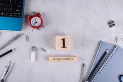 Ordinateur portable, réveil rouge et approvisionnements, calendrier en bois avec date le 1er septembre sur un bureau concret gris Image stock