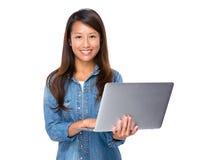 Ordinateur portable singapourien d'utilisation de femme ordinateur-ordinateur Photo stock
