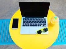 ordinateur portable, smartphone et lunettes de soleil sur la table Image stock
