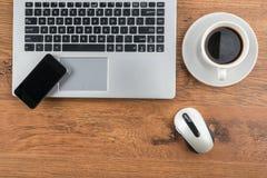 Ordinateur portable, smartphone et souris avec du café sur le bureau Image stock