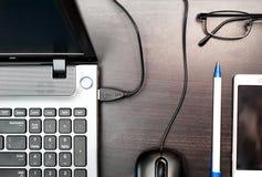 Ordinateur portable, souris d'ordinateur, téléphone portable, verres et stylo sur la table Photographie stock