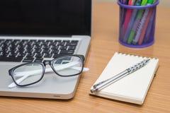 Ordinateur portable, stylo, note et verres vides d'affaires sur la table en bois Photo libre de droits