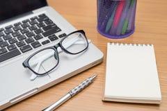 Ordinateur portable, stylo, note et verres vides d'affaires sur la table en bois Photos stock