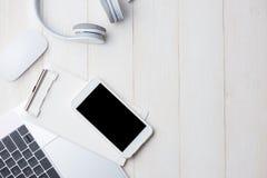Ordinateur portable sur la table blanche avec l'écouteur et le smartphone vi Photo stock