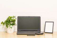 Ordinateur portable sur la table en bois avec le cadre de photo, usine de lierre dans le pot, stylo, téléphone intelligent L'espa Image stock