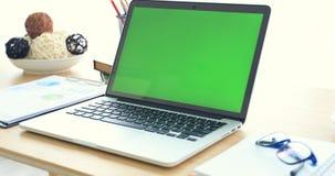Ordinateur portable sur le bureau avec l'écran vert clips vidéos