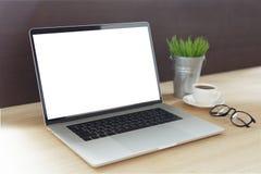 Ordinateur portable sur le bureau de travail montrant à écran blanc la vue de côté Photographie stock