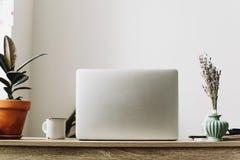 Ordinateur portable sur le bureau en bois avec le téléphone, le carnet, la tasse de café et le pl Photo libre de droits