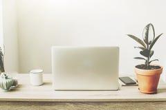 Ordinateur portable sur le bureau en bois avec le téléphone, le carnet, la tasse de café et le pl Image libre de droits