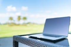 Ordinateur portable sur le fond de tache floue de terrain de golf avec l'espace, les affaires ou le travail de copie n'importe où Photos stock