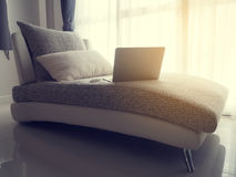 Ordinateur portable sur le sofa moderne au salon avec la lumière du soleil chaude dans Photographie stock