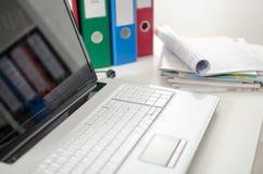 Ordinateur portable sur un bureau avec des reliures et des magazines Images stock