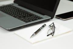 Ordinateur portable, téléphone, bloc-notes, stylo, verres Photographie stock
