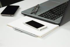 Ordinateur portable, téléphone, bloc-notes, stylo, verres Image libre de droits