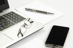 Ordinateur portable, téléphone, bloc-notes, stylo, verres Images stock