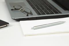 Ordinateur portable, téléphone, bloc-notes, stylo, verres Photos libres de droits