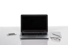 Ordinateur portable, téléphone, stylo, bloc-notes, verres Image libre de droits