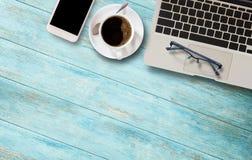 Ordinateur portable, verres et tasse de café sur la table en bois Photos libres de droits