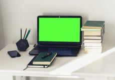 Ordinateur portable vert d'écran, pile de livres, carnet et crayons sur la table blanche, fond de concept de bureau d'éducation images stock