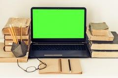 Ordinateur portable vert d'écran, pile de vieux livres, carnet et crayons sur la table blanche, fond de concept de bureau d'éduca photo libre de droits