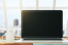 Ordinateur portable vide sur le bureau dans un bureau ensoleillé avec une tasse de coff Photos stock