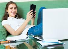 ordinateur portatif à la maison de fille utilisant des jeunes Images stock