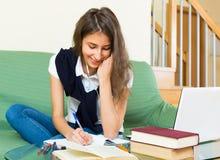 ordinateur portatif à la maison de fille utilisant des jeunes Photo libre de droits