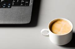 Ordinateur portatif avec la cuvette de café Image libre de droits