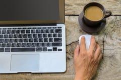 Ordinateur portatif avec la cuvette de café Photographie stock