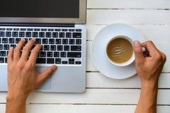Ordinateur portatif avec la cuvette de café Photographie stock libre de droits