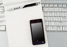 Ordinateur portatif avec le téléphone portable et le bloc-notes de pointe. Images libres de droits