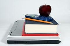 Ordinateur portatif, calculatrice, livres, pomme et crayon Photos stock