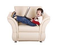 ordinateur portatif d'écouteur de garçon Photographie stock libre de droits