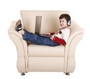 ordinateur portatif d'écouteur de garçon Photographie stock