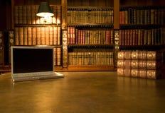 Ordinateur portatif dans la bibliothèque classique Photo stock
