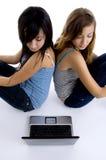 ordinateur portatif de filles regardant à Images libres de droits