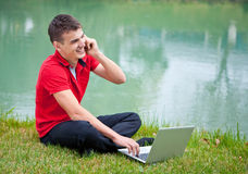 Ordinateur portatif de mobile de jeune homme Photo libre de droits
