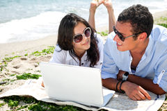 Ordinateur portatif de plage de couples Photographie stock libre de droits