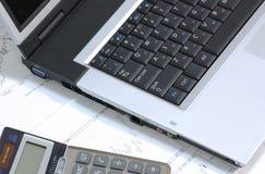 Ordinateur portatif et calculatrice sur des diagrammes de finances Photographie stock libre de droits