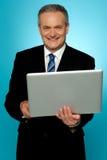 Ordinateur portatif exécutif âgé de sourire de fixation Image libre de droits