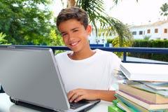 Ordinateur portatif fonctionnant d'adolescent de garçon heureux d'étudiant Image stock