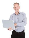 Ordinateur portatif heureux de fixation d'homme d'affaires Images stock
