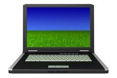 Ordinateur portatif noir avec l'herbe et le ciel sur l'écran Photos stock