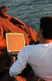 Ordinateur portatif parmi des roches Images libres de droits