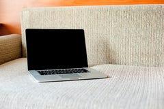 Ordinateur portatif sur le sofa Fonctionner à la maison indépendant Photos stock