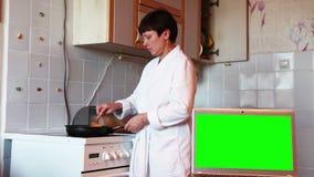 Ordinateur portatif sur un bureau Écran vert La femme prépare le dîner banque de vidéos