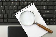 Ordinateur portatif, un cahier et un lupe. images stock